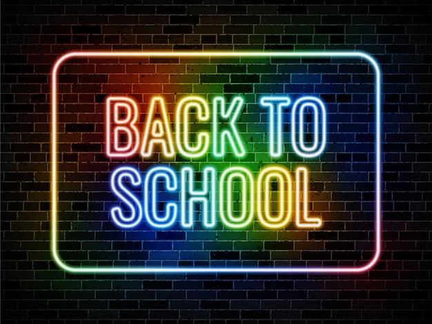 Torna a scuola insegna al neon su sfondo scuro muro di mattoni Vettore Premium