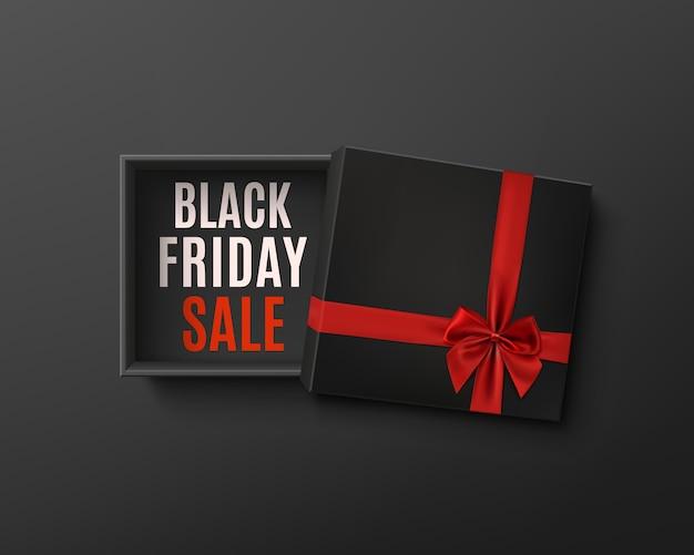 Progettazione di vendita del black friday. contenitore di regalo vuoto nero aperto con nastro rosso e fiocco su sfondo scuro. vista dall'alto. modello per il design della presentazione, banner, brochure o poster. Vettore Premium