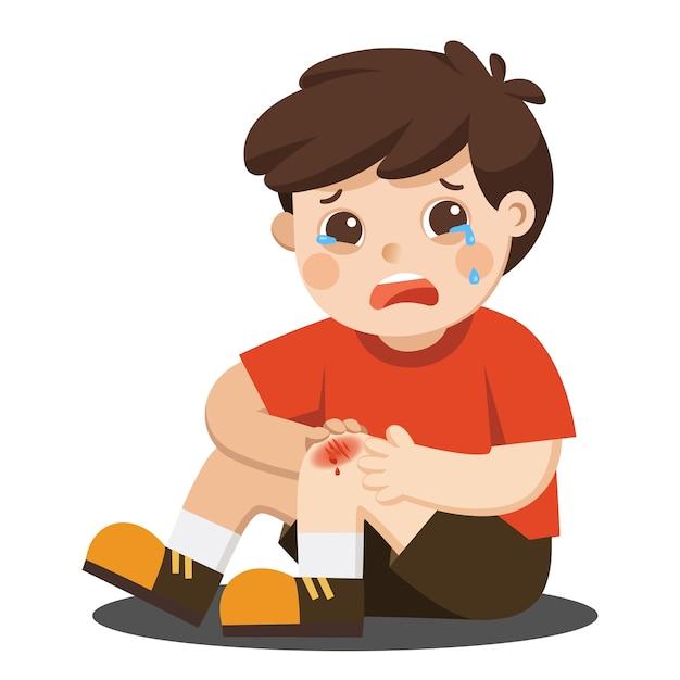 Un ragazzo che tiene graffio doloroso del ginocchio della gamba ferita Vettore Premium