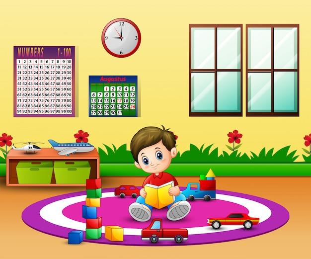 Un ragazzo che legge un libro sul tappeto rotondo in aula Vettore Premium
