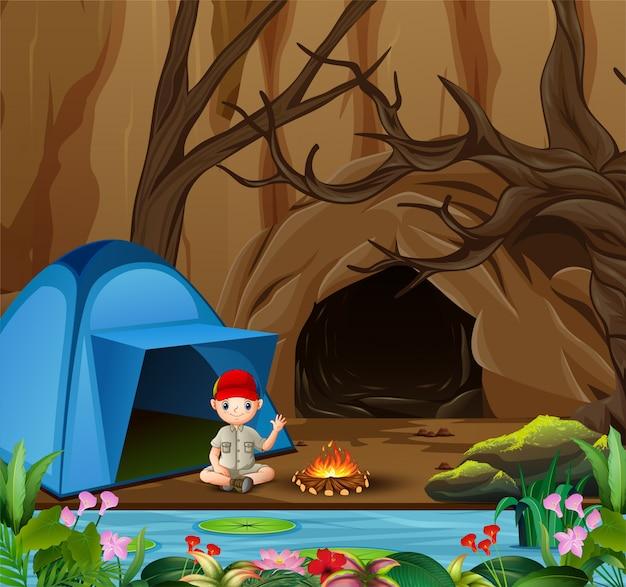 Boy scout seduto al campeggio Vettore Premium