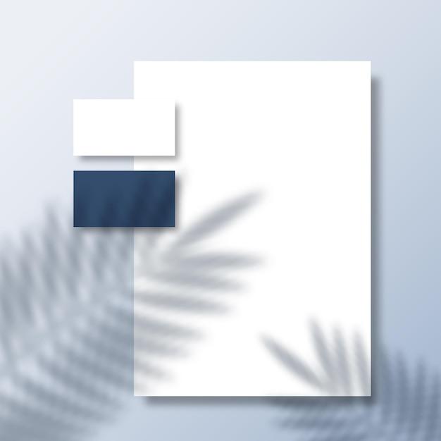 Biglietti da visita e carta intestata su una superficie con copertura ombreggiata di foglie di palma e felce tropicale Vettore Premium