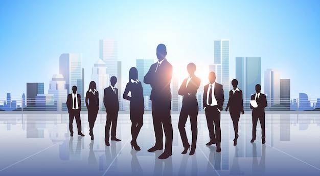 Silhouette di uomini d'affari in piedi sopra la città moderna Vettore Premium