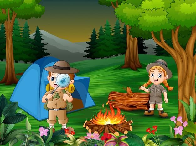 Cartone animato di bambini che si accampano nella foresta Vettore Premium
