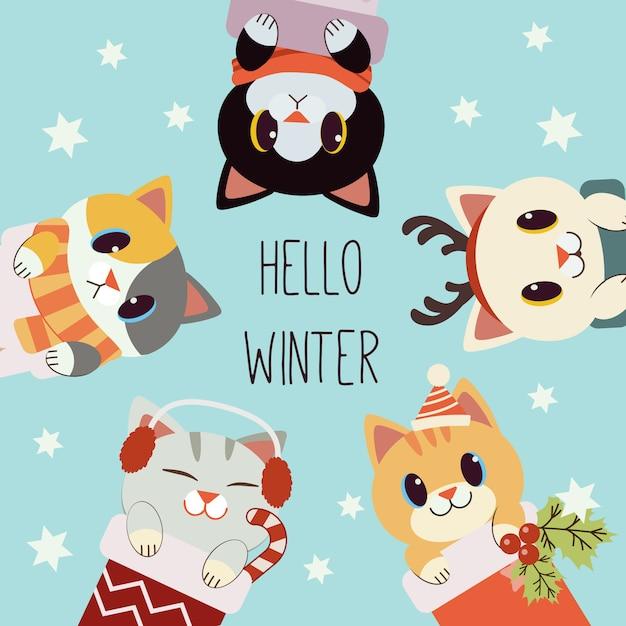 Il personaggio del simpatico gatto con il testo di ciao inverno nel tema natale. il simpatico gatto indossa sciarpa, corno di cervo, paraorecchie e cappello invernale. il personaggio del simpatico gatto in stile piatto. Vettore Premium