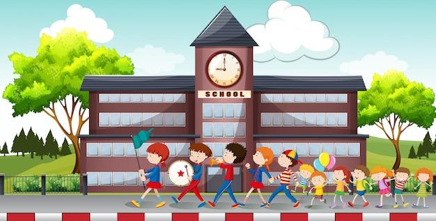 I bambini in marcia davanti a scuola Vettore Premium