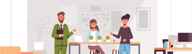 Coppia di colleghi che punta a una nuova impiegata femminile presentando un lavoratore assunto all'interno della squadra moderna centro di lavoro interno ufficio interno Vettore Premium