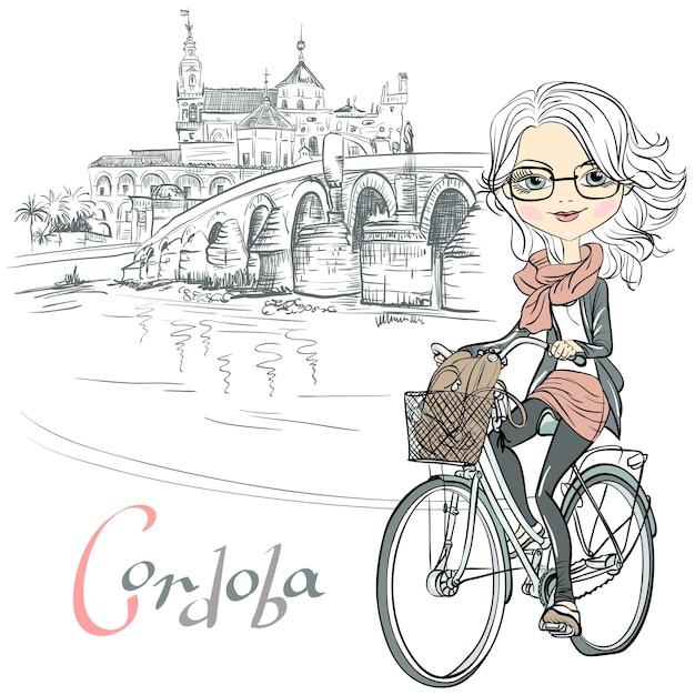 Carina bella ragazza alla moda va in bicicletta a cordoba, andalusia, spagna. moschea mezquita e ponte romano sullo sfondo Vettore Premium
