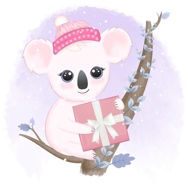 Koala carino e confezione regalo sull'albero nella stagione invernale Vettore Premium