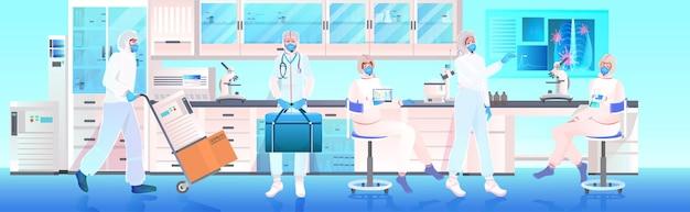 Team di medici in maschere e tute protettive che lavorano insieme nello sviluppo di vaccini di laboratorio medico Vettore Premium
