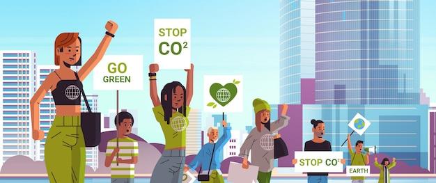 Attivisti ambientali in possesso di manifesti andare verde salvare il concetto di sciopero del pianeta manifestanti che fanno una campagna per proteggere la terra dimostrando contro il riscaldamento globale ritratto paesaggio urbano sfondo orizzontale Vettore Premium