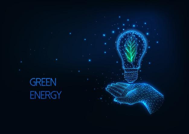 Futuristico verde, concetto di energia rinnovabile con incandescente bassa mano poligonale che tiene lampadina Vettore Premium