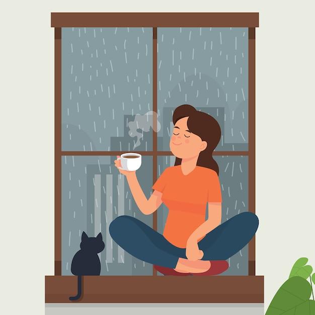 Ragazza bere tè / caffè vicino alla finestra mentre fuori la pioggia Vettore Premium