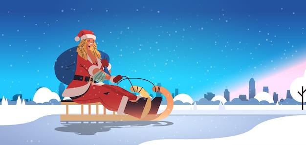 Ragazza in costume da babbo natale in sella alla slitta felice anno nuovo buon natale vacanze celebrazione concetto inverno paesaggio urbano sfondo orizzontale a figura intera illustrazione vettoriale Vettore Premium