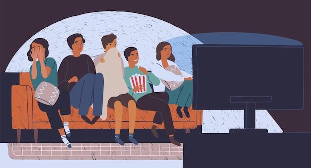 Gruppo di amici seduti sul divano nell'oscurità e guardare film horror Vettore Premium