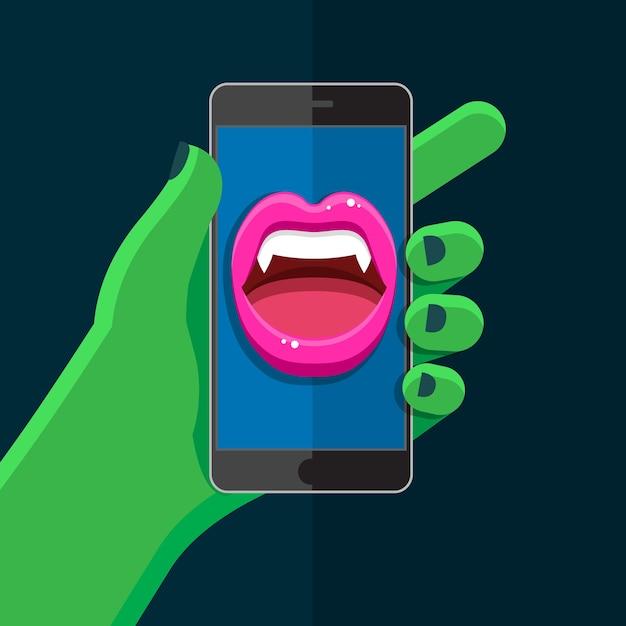 Concetto di halloween. mano verde che tiene un telefono con la bocca di vampiro parlante con labbra rosse aperte e zanne in mostra. Vettore Premium