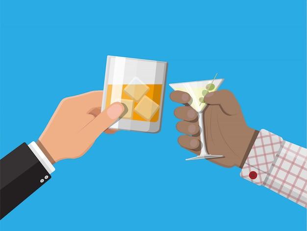 Le mani raggruppano i vetri della tenuta con le bevande Vettore Premium