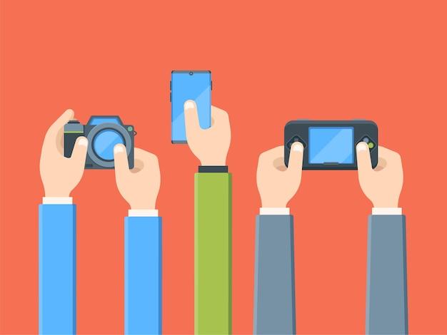 Mani con dispositivi digitali piatti. fotocamera, smartphone, gioco portatile. persone con l'elettronica. intrattenimento, tecnologia mobile. Vettore Premium