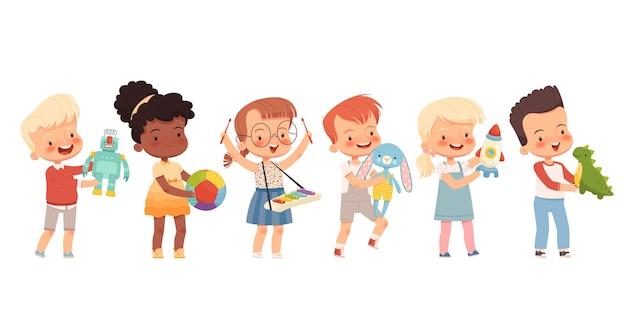 I bambini felici giocano con diversi giocattoli, li tengono nelle loro mani. bambini divertenti di diverse nazionalità con i giocattoli preferiti. piatto del fumetto. isolato su uno sfondo bianco. Vettore Premium
