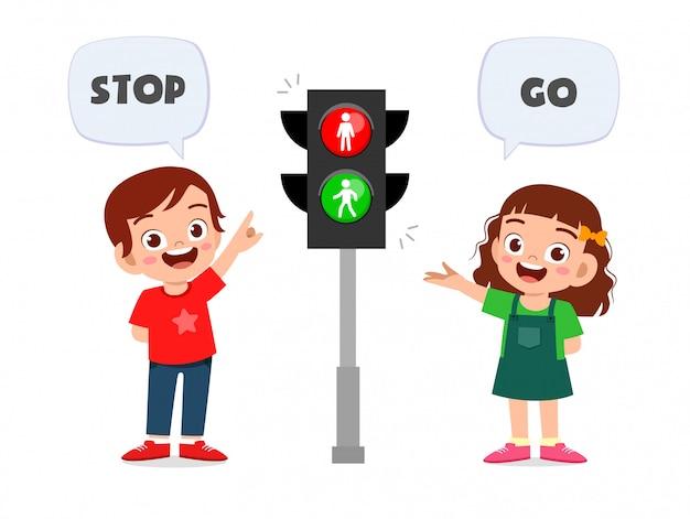 Ragazzo e ragazza svegli felici del bambino con il segnale stradale Vettore Premium