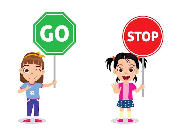 Le ragazze sveglie felici del bambino che tengono il segnale stradale si fermano e vanno isolato su priorità bassa bianca Vettore Premium