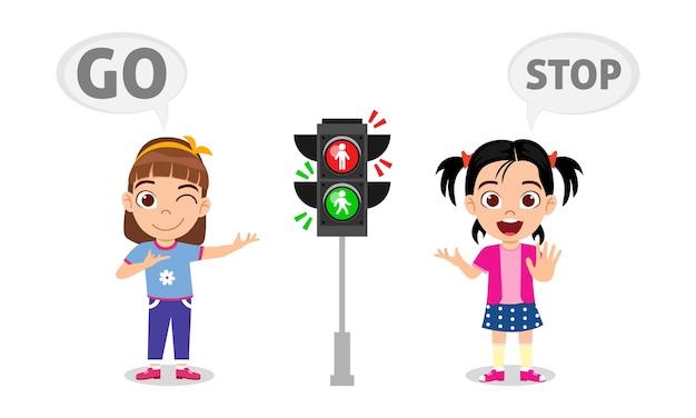Ragazze del bambino sveglie felici con il segnale stradale si fermano e vanno Vettore Premium