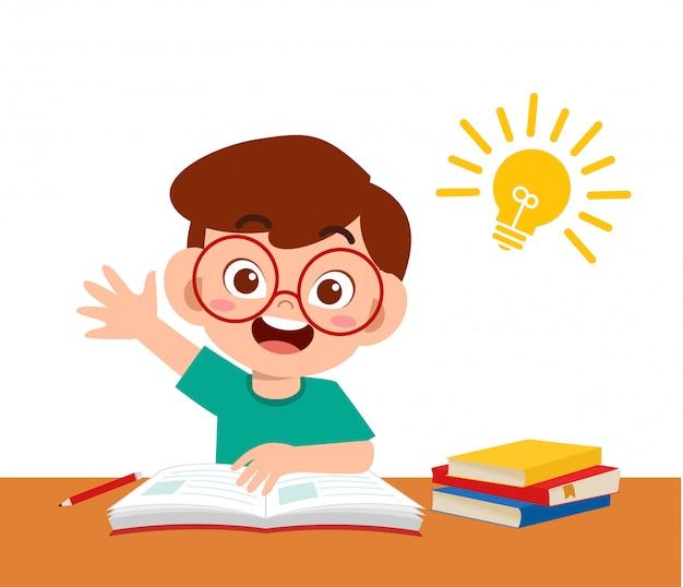 Felice ragazzo carino studiare i compiti con l'idea Vettore Premium