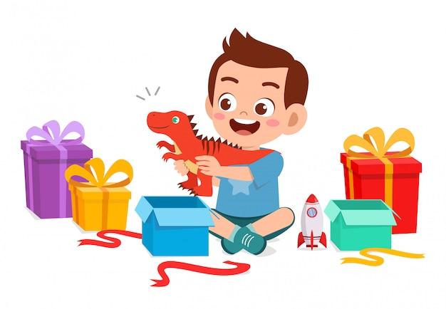 Regalo aperto del ragazzo sveglio felice del bambino piccolo dal compleanno Vettore Premium