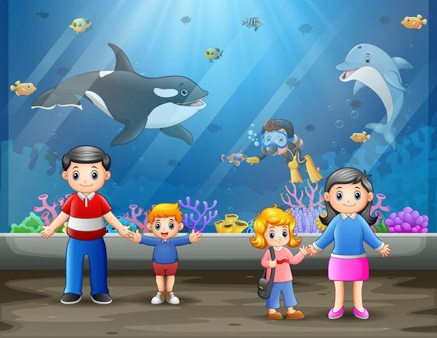Una famiglia felice in acquario marino Vettore Premium