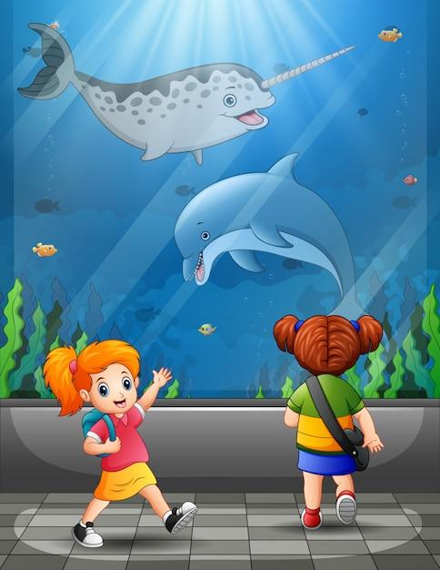 I bambini felici che esaminano l'oceano pesca l'acquario Vettore Premium