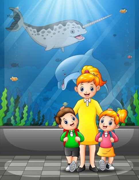 Bambini felici che visitano un'escursione dell'acquario con la madre Vettore Premium