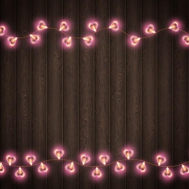 Lampada a forma di cuore per posto di decorazione su fondo in legno. Vettore Premium
