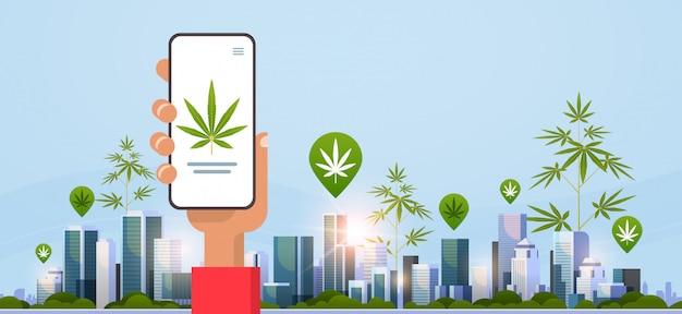 Mano umana che tiene smartphone trafficante di droga ordine cannabis canapa marijuana o medicina online acquisto droghe concetto mobile app paesaggio urbano sfondo orizzontale piatta Vettore Premium