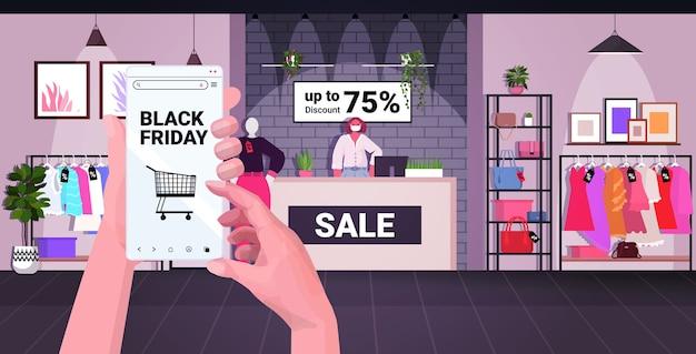Mani umane utilizzando smartphone acquistare vestiti nell'app mobile venerdì nero shopping grande vendita coronavirus quarantena concetto negozio di moda interno illustrazione vettoriale orizzontale Vettore Premium
