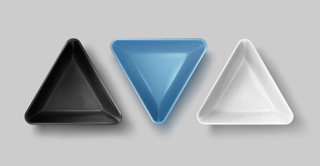 Illustrazione di ciotole in ceramica triangolari nere, blu e bianche vuote su sfondo grigio, vista dall'alto Vettore Premium