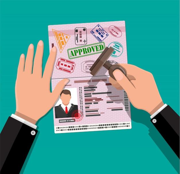 Passaporto internazionale e timbro in mano Vettore Premium