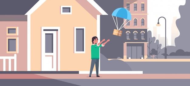 Uomo che cattura la scatola pacchi cadendo con il paracadute dal cielo trasporto pacchetto di spedizione posta aerea espresso concetto di consegna moderna casa edificio esterno a figura intera orizzontale piatta Vettore Premium