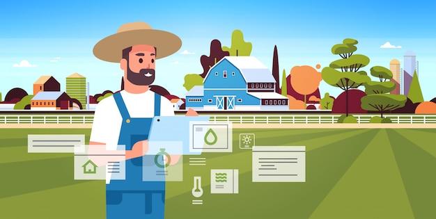 Uomo agricoltore con condizione di monitoraggio tablet controllo organizzazione di prodotti agricoli di raccolta intelligente concetto agricolo paesaggio agricolo paesaggio Vettore Premium