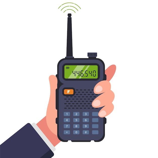 L'uomo tiene un walkie-talkie in mano per la comunicazione. Vettore Premium