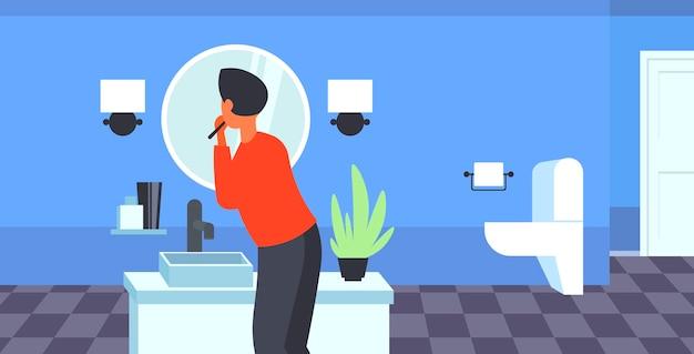Uomo che guarda allo specchio lavarsi i denti con spazzolino da denti sanità igiene dentale concetto moderno bagno interno vista posteriore ritratto Vettore Premium