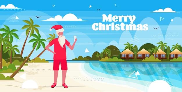 Uomo che indossa il cappello di babbo natale utilizzando lo smartphone sulla spiaggia tropicale capodanno vacanze di natale vacanza Vettore Premium