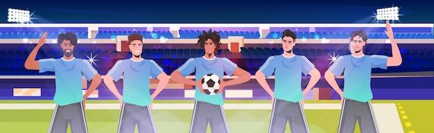 Mescolare i giocatori di calcio da corsa in piedi insieme sulla squadra di calcio dello stadio pronti per iniziare il ritratto orizzontale della partita Vettore Premium