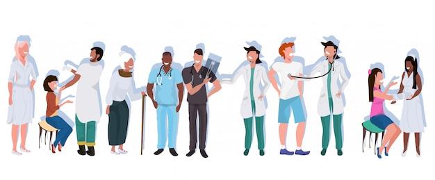 Mescolano i medici della corsa con i pazienti che stanno insieme i lavoratori ospedalieri nell'orizzontale piano integrale di concetto professionale uniforme della medicina di sanità di occupazione professionale Vettore Premium