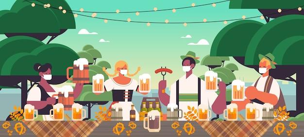 Mescolare gente di razza in maschere per il viso bere birra oktoberfest festival celebrazione concetto sullo sfondo del paesaggio Vettore Premium