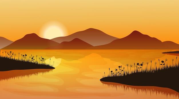 Paesaggio di montagna al tramonto. sagoma di erba sopra l'acqua e la catena montuosa. Vettore Premium