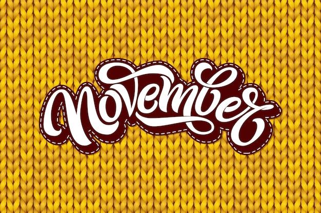 Lettering di novembre sulla trama di maglia gialla. calligrafia moderna pennello con motivo a maglia senza soluzione di continuità. scritte per biglietto di auguri, banner di social media, stampa. illustrazione. Vettore Premium