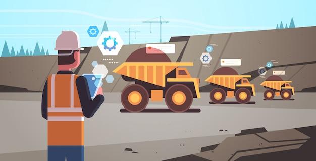 Lavoratore uomo a cielo aperto nel casco utilizzando app mobile controllo dumper Vettore Premium