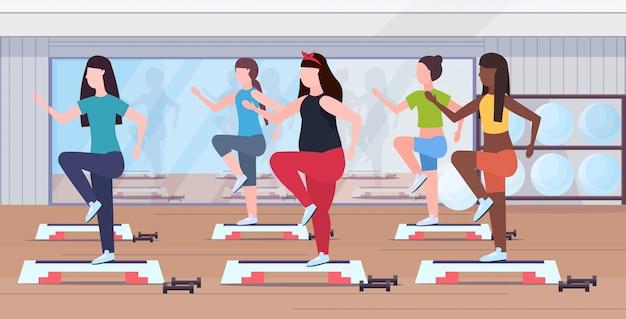 Gruppo di donne in sovrappeso facendo squat sulla piattaforma passo ragazze mix di allenamento in palestra aerobica allenamento perdita di peso concetto moderno centro benessere studio interno orizzontale Vettore Premium
