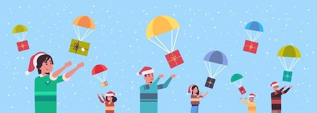 Persone che catturano regali presenti scatole cadendo con paracadute buon natale felice anno nuovo festa celebrazione concetto uomini donne che indossano cappelli di babbo natale ritratto orizzontale illustrazione vettoriale Vettore Premium