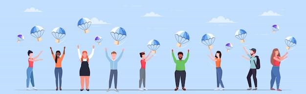La gente che cattura le scatole dei pacchi che cadono con il paracadute dal trasporto del cielo pacchetto di spedizione posta aerea espresso concetto di consegna postale orizzontale integrale Vettore Premium